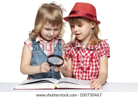 Closeup of two little girls reading a book through the magnifying glass, over white background - stock photo