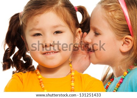 Closeup of two little 6-7 years old Asian and Caucasian girls gossip telling secrets mouth to ear, isolated on white - stock photo