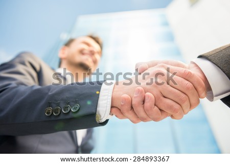 Closeup of two successful smiling business men shaking hands. - stock photo