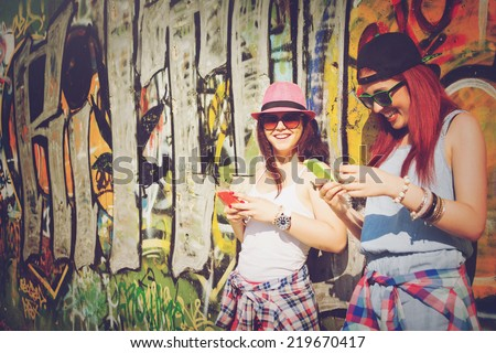 Closeup of two teenage girls with smart phones. Two young women using smartphones against colorful graffiti wall. - stock photo