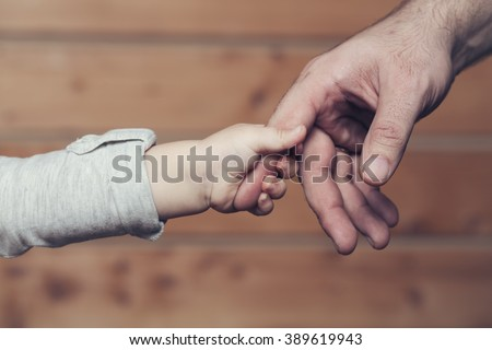 Closeup of two touching hands of small baby boy holding finger of male father as symbol of family love and trust on blurred wooden background, horizontal picture - stock photo