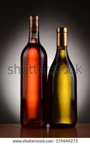 Closeup of two wine bottles backlit with a light to dark gray background. Blush and Chardonnay bottles are shown in full length. Vertical Format. - stock photo
