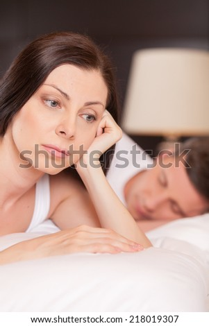 closeup of unhappy woman lying in bed stressed. couple having problem while man sleeping - stock photo