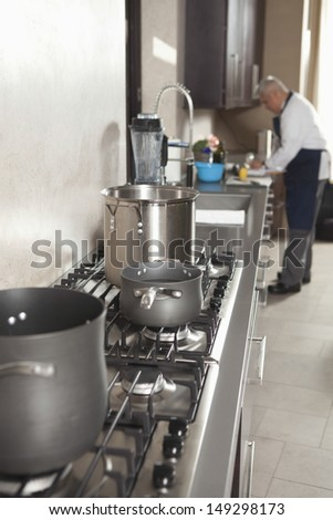 Closeup of utensils on stove with chef working in background at commercial kitchen - stock photo