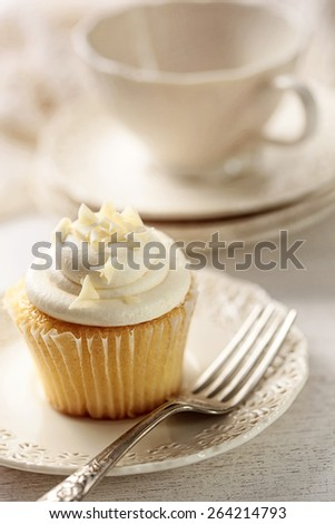 Closeup of vanilla cupcake with tea cup in background - stock photo