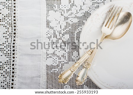Closeup of vintage lacy white cloth handmade German silver fork and spoon on a white ceramic plate. selective Focus - stock photo