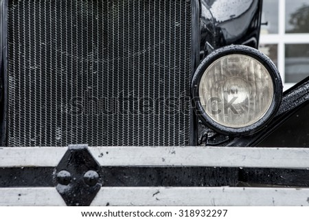 closeup of vintage 1920's car with grill and headlamp - stock photo