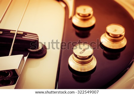 Closeup of volume  and  tone knobs of  vintage electric guitar, selective focus. Processed with vintage style. - stock photo