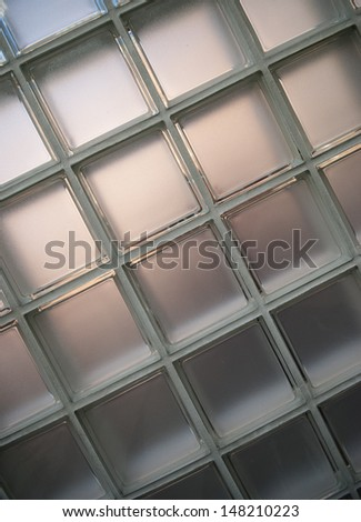Closeup of wall of glass blocks with reflected colors from windows. - stock photo