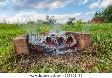 Closeup of warm fire burning in a campfire at the outdoors - stock photo