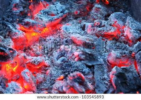 Closeup of warm glowing embers in fireplace; white and gray ash - stock photo
