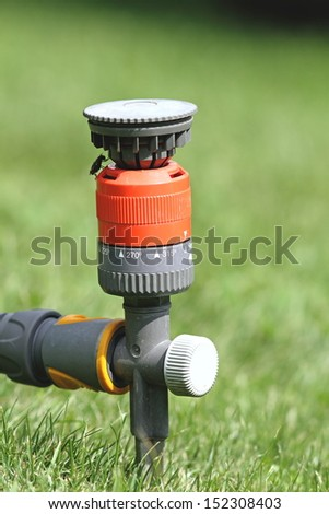 closeup of water sprinkler in the green grass of the garden - stock photo