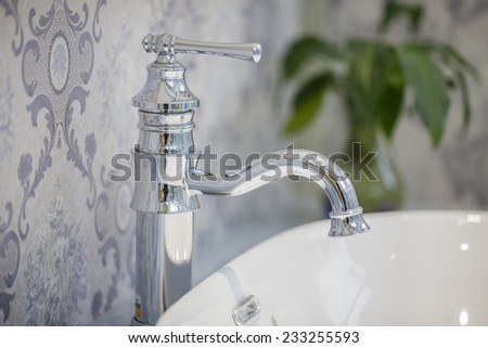 Closeup of water-supply faucet isolated in modern bathroom - stock photo