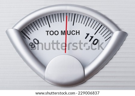 Closeup of weight scale indicating Too Much weight - stock photo