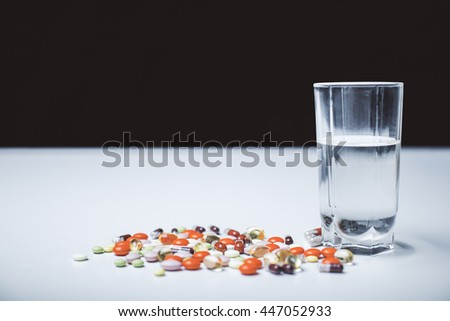Closeup of white tabletop with colorful pills and glass of water on dark background - stock photo