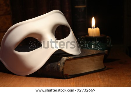 Closeup of white venetian mask lying on vintage old book near lighting candle - stock photo