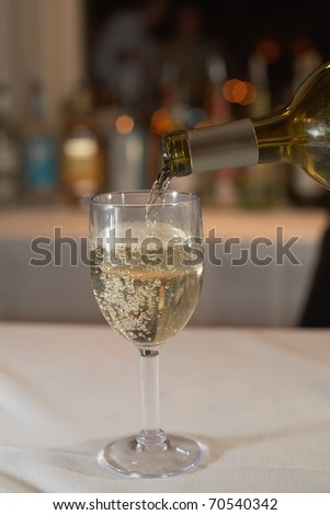 Closeup of white wine be poured at bar - stock photo