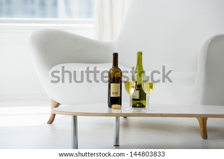 Closeup of wine glasses and bottles on coffee table in living room - stock photo