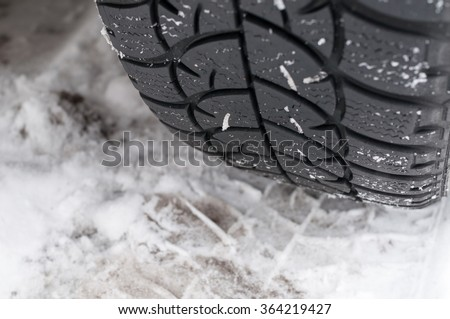 Closeup of Winter tyre on the road covered with snow - stock photo