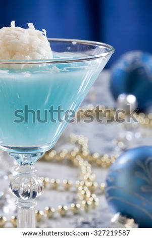 Closeup of Winter Wonderland Cocktail, garnished with coconut vanilla ice cream ball on Christmas decorated holiday table with Christmas ornaments. Holiday cocktails series.