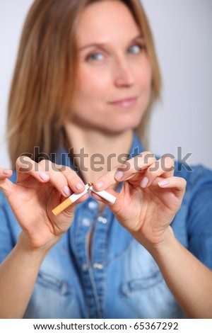 Closeup of woman breaking cigarette - stock photo