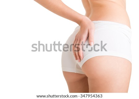 Closeup of woman examining her buttocks looking dor cellulite, isolated in white - stock photo