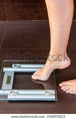 Closeup of woman foot uploading to bathroom scale. Health and weight concept - stock photo