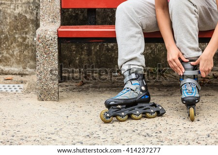 Closeup of woman girl putting on roller skates outdoor. - stock photo