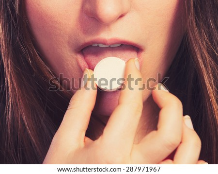 Closeup of woman girl taking swallowing painkiller pill tablet. Health care. Headache and pain. - stock photo
