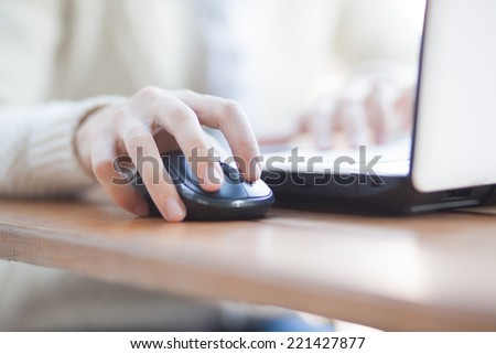 Closeup of woman hand clicking mouse outdoor - stock photo