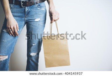 Closeup of woman hand holding blank craft paper bag with handles, mock-up of brown package - stock photo