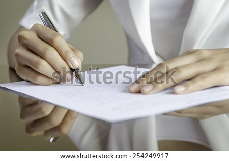 closeup of woman hands signing a contract - stock photo