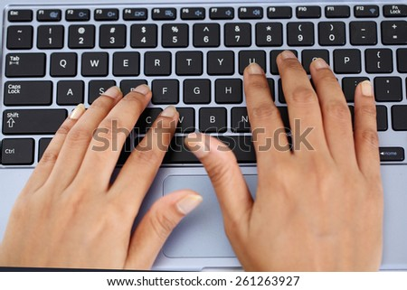 Closeup of woman hands typing on laptop keyboard - stock photo