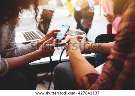 Closeup of woman is reading text message on mobile phone in network, while is sitting with laptop computer in co-working cafe. Group of friends are using gadgets during recreation time in coffee shop  - stock photo