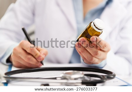 Closeup of woman medic writing medical record. Concept of doctor visit, examination and treatment. Shallow depth of field. - stock photo