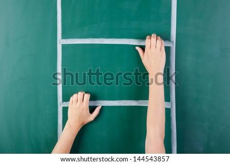 Closeup of woman's hand climbing ladder drawn on green board - stock photo