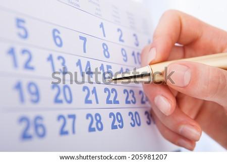 Closeup of woman's hand marking date 15 on calendar - stock photo