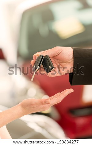 Closeup of woman's hand receiving car keys from agent - stock photo