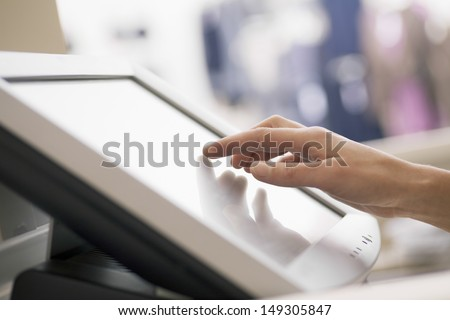 Closeup of woman's hand touching screen of cash register in store - stock photo