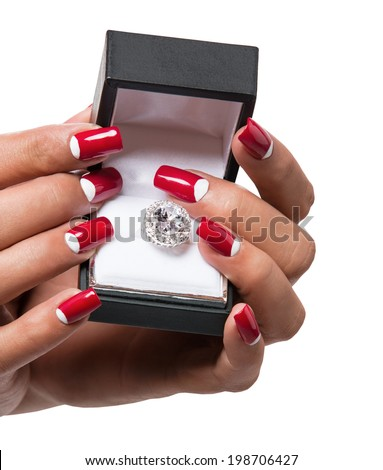 closeup of woman's hand with red manicure holding a box with white gold engagement ring on a white studio background  - stock photo