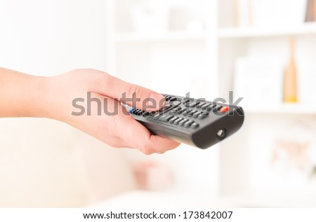 closeup of woman's hand with remote controller at home - stock photo
