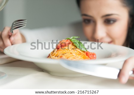 Closeup of woman's hands holding fork and knife. young girl looking at food in restaurant - stock photo