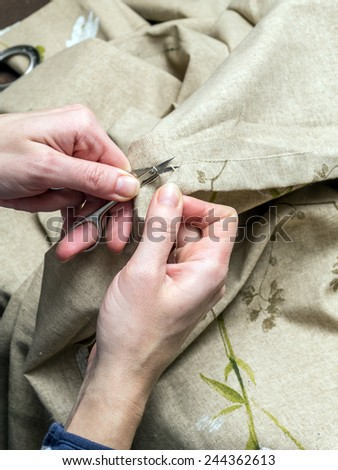 Closeup of woman's hands unraveling fabric border using scissors - stock photo