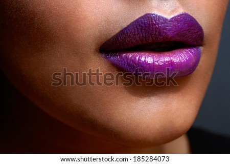 closeup of woman�¢??s sexy lips with purple ombre style lipstick on tanned skin - stock photo