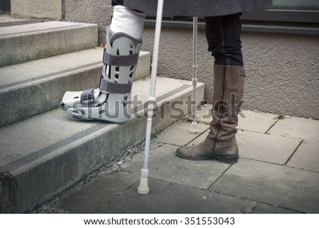 closeup of woman walking with a plaster cast and crutches - stock photo