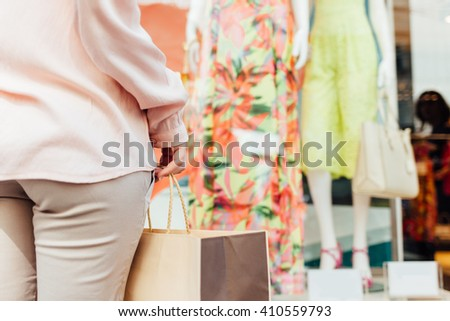 Closeup of woman with shopping bag in front of boutique showcase with copy space - stock photo
