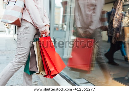 Closeup of woman with shopping bags looking at boutique showcase with copy space - stock photo