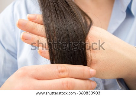 closeup of woman with straight hair touching her hair and checking its health - stock photo