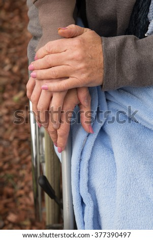 closeup of women hands, one of them in a wheelchair - stock photo