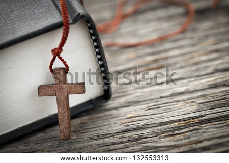 Closeup of wooden Christian cross necklace next to holy Bible - stock photo